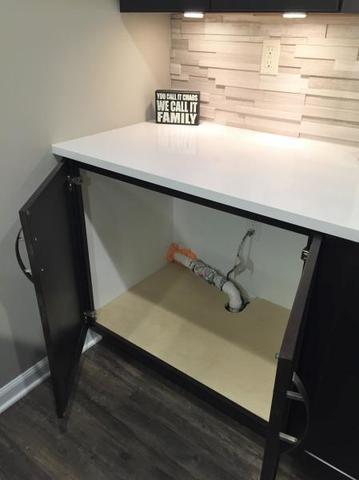 Sump pump hidden in basement bar cabinet in a Shelby Township, MI home