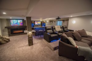 basement finished with carpeting and a theater space with platform seating and a blue led bar
