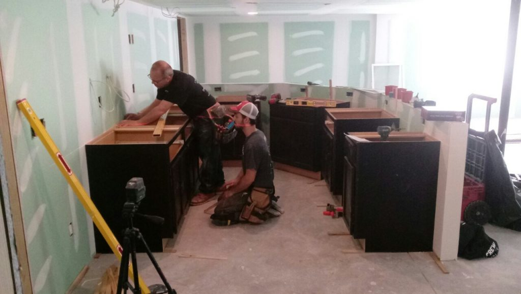 carpenters working on finishing cabinets in basement