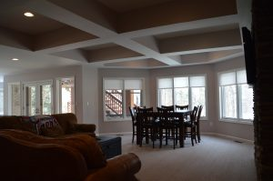 basement with large windows looking into backyard and detailed ceiling