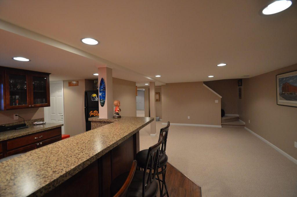 finished basement with bar and carpeted living room