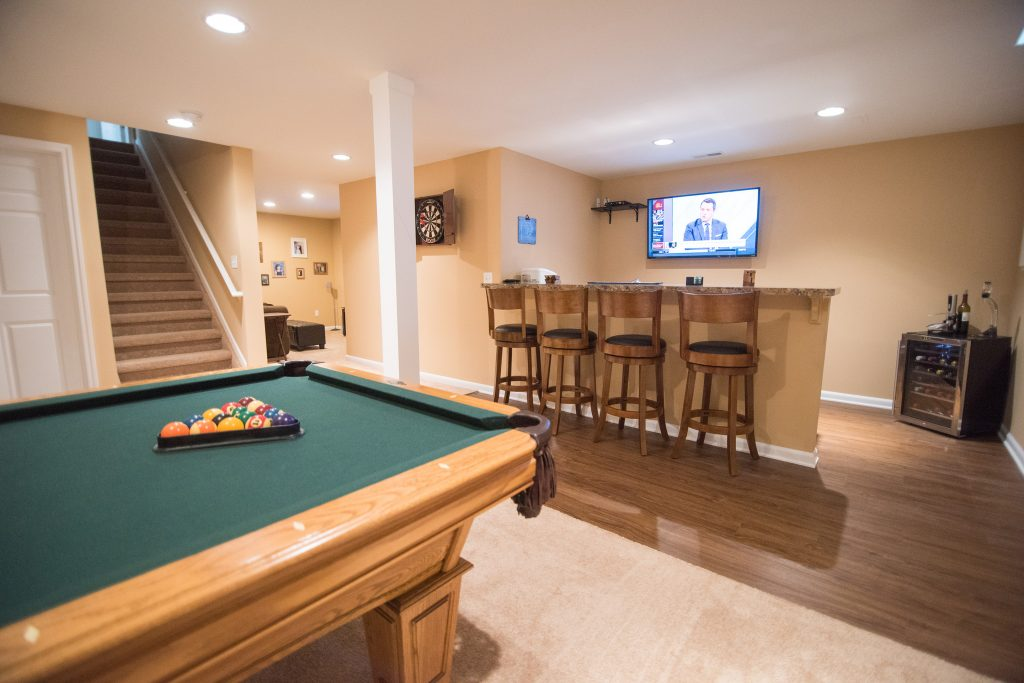 finished basement with carpeting and vinyl plank flooring