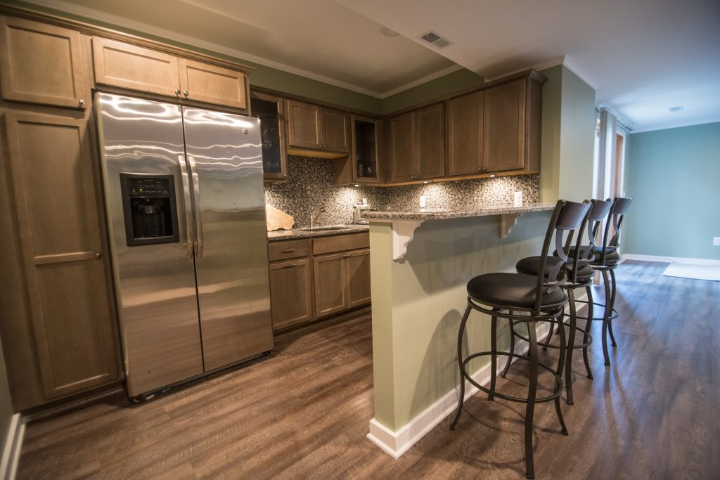kitchen in finished basement with vinyl plank flooring and bar seating