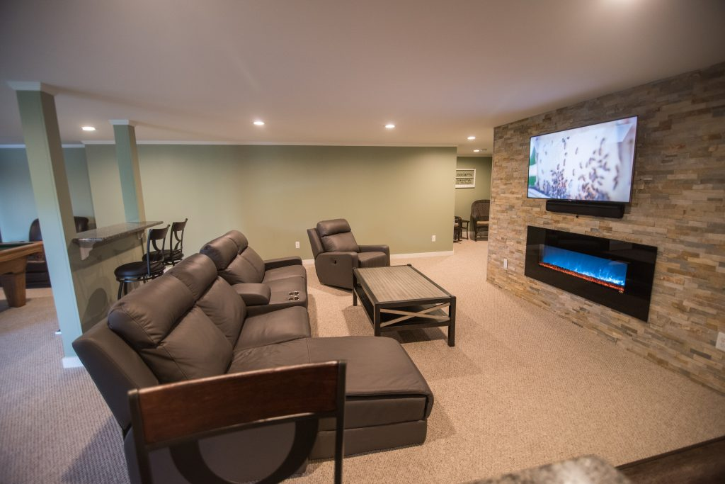 large open living room space with electric fireplace and recliners