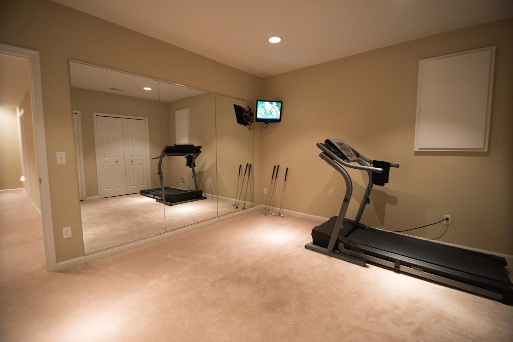 basement fitness room with mirrored wall and carpet