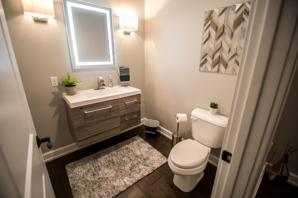 bright and modern industrial basement bathroom with floating vanity