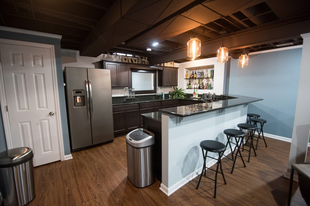 bar area in basement with painted ceiling and dark cabinets