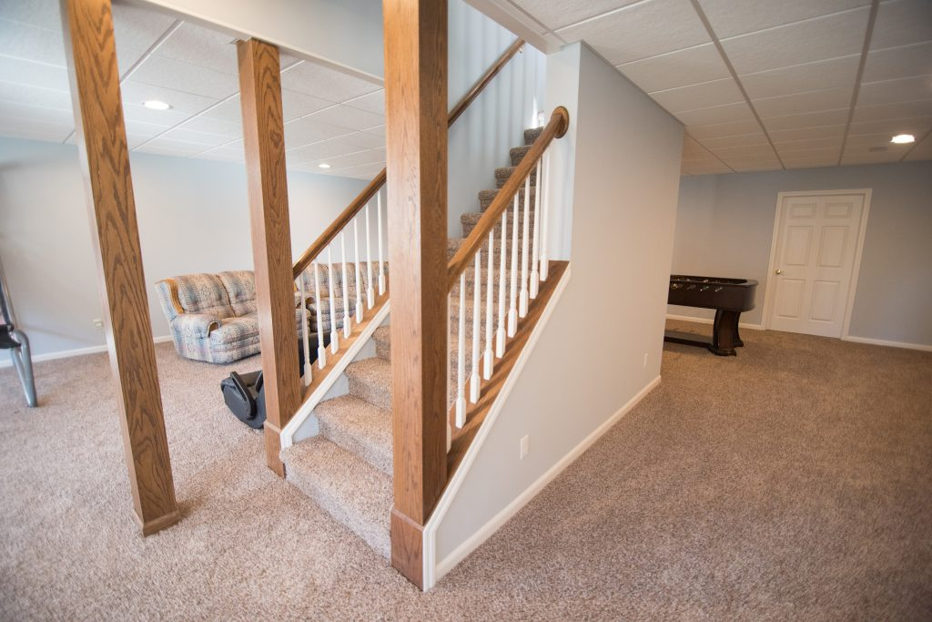 new finished basement with staircase finished with carpet