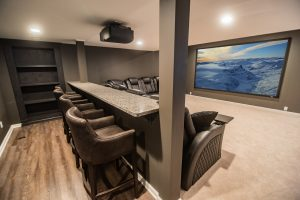 custom basement theater with bar style seating behind sectional in Novi, MI