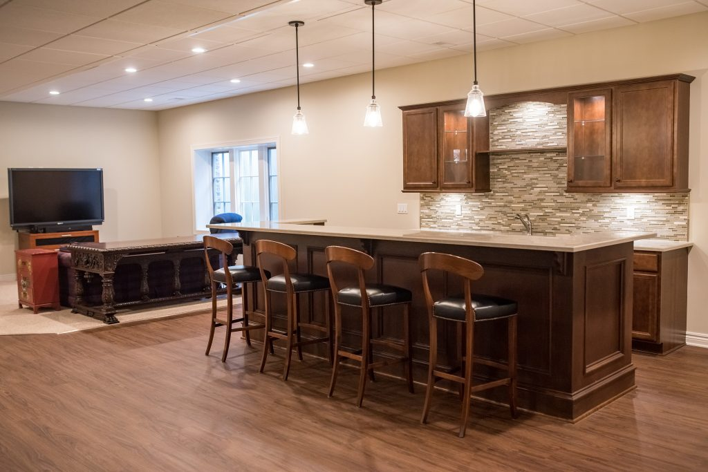 basement with high ceilings and custom bar area with granite countertops