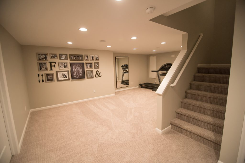 open staircase in basement with exercise room