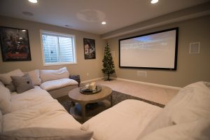 finished basement with white sofa and a projection screen on the wall showing a movie