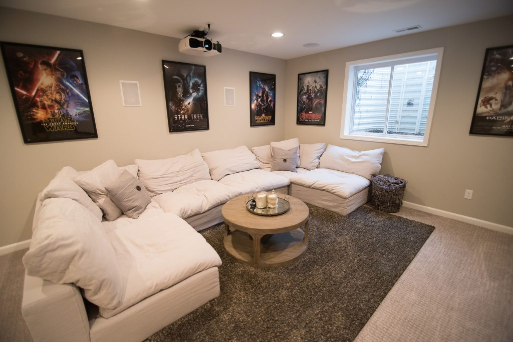 large cozy sectional in finished basement with carpeting and bright design