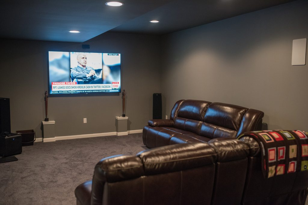 basement media room with large tv for movies and sports