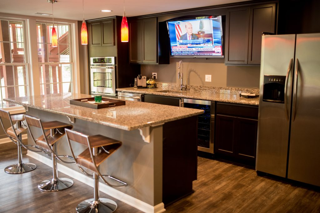 finished basement with kitchen space and large island with seating