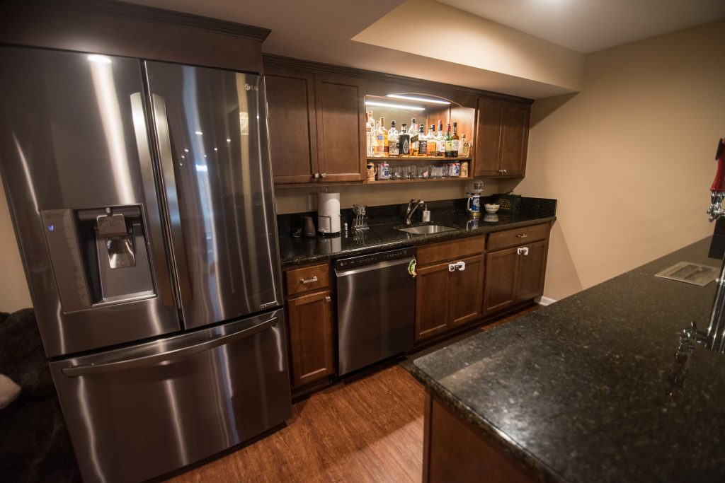 basement kitchen with full size fridge and dishwasher
