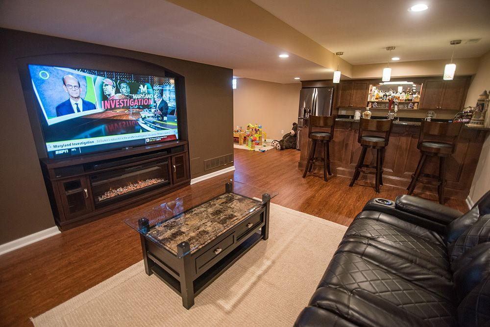 living room in basement with vinyl plank flooring and arch for TV