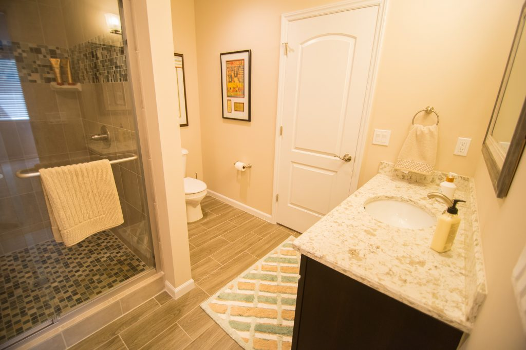 full bathroom in basement with vinyl tile and shower