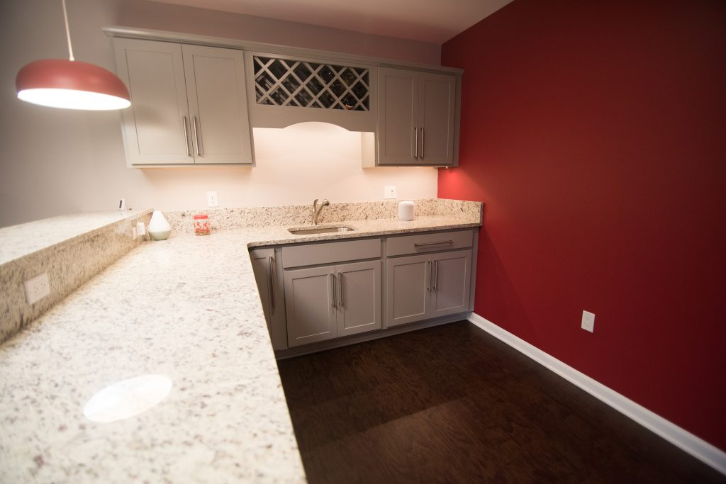 white cabinets and white granite in basement bar with vinyl plank