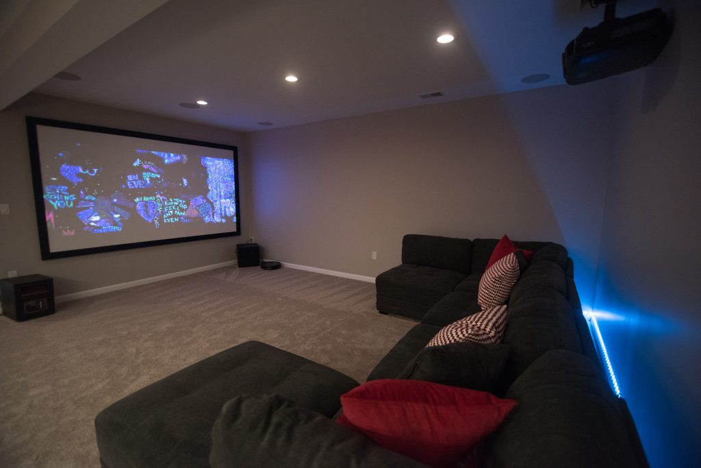 movie theater room in basement with large sectional and projection tv