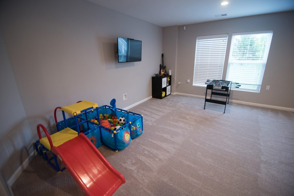 basement finishing carpet with TV area for the kids