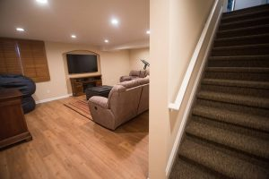 basement staircase leading to finished basement with vinyl plank