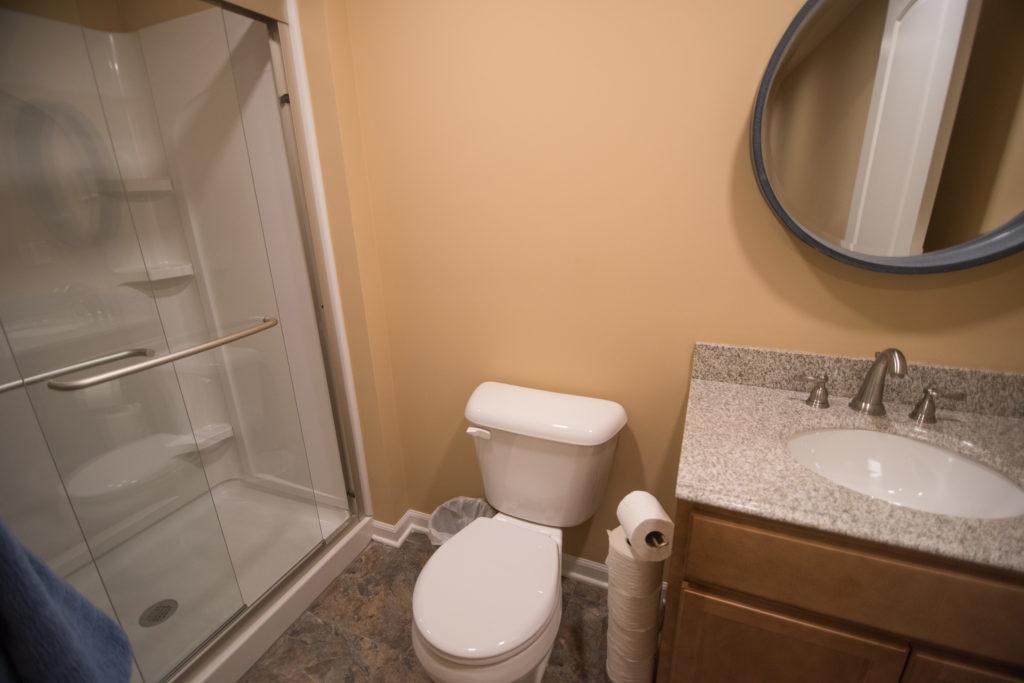 small basement bathroom with vinyl tile and granite countertop vanity