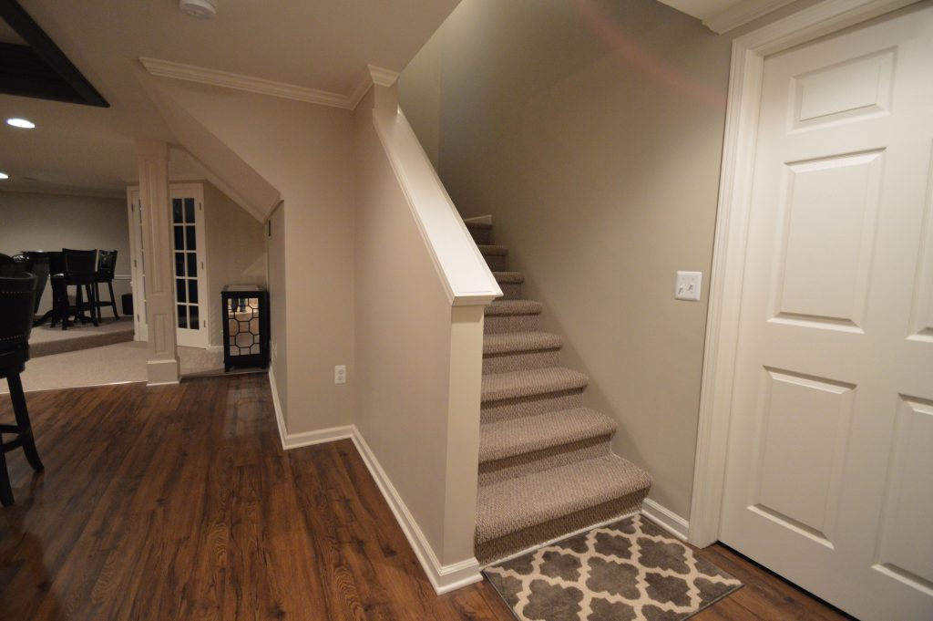 basement staircase with open view railing and carpet on the treads
