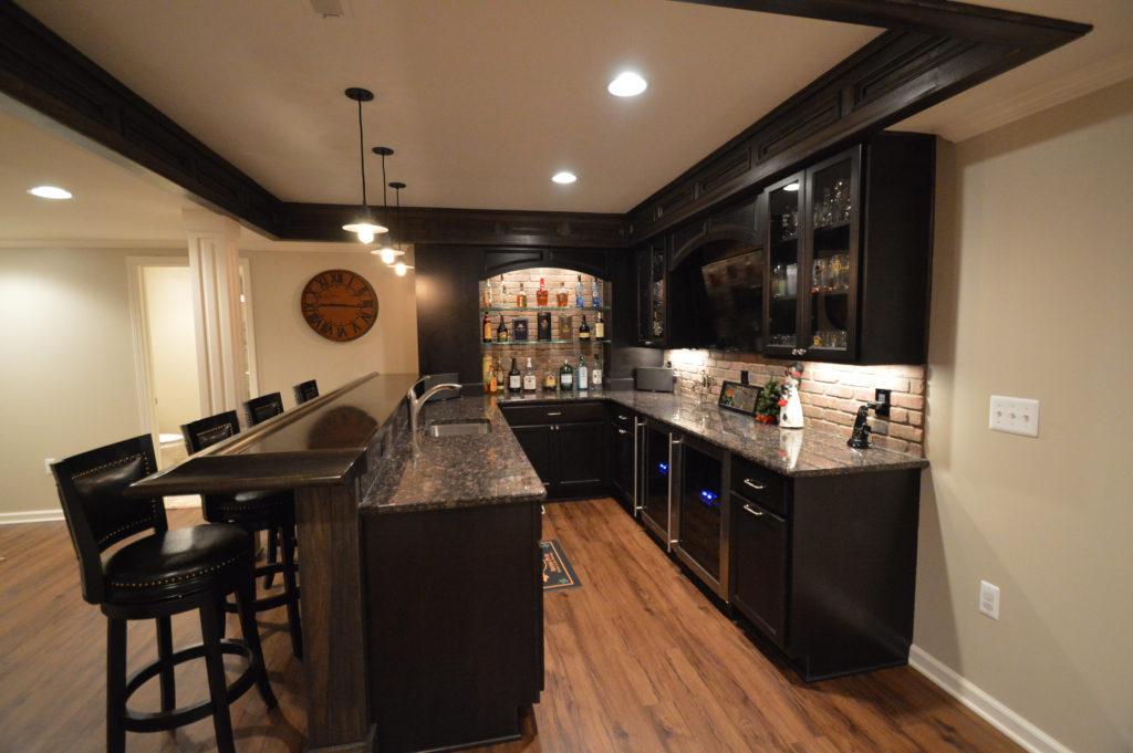 basement bar with granite countertops and vinyl plank flooring