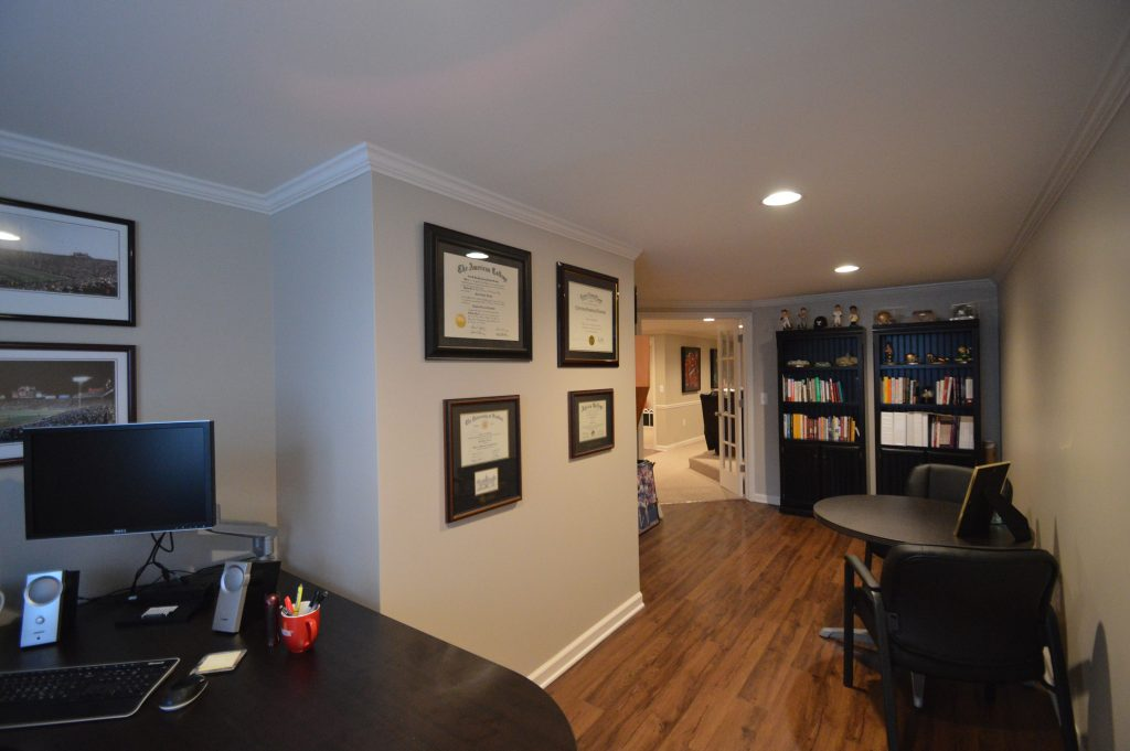 basement home office with vinyl plank flooring and shelving