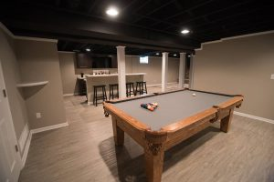 basement with painted ceiling and grey vinyl plank flooring