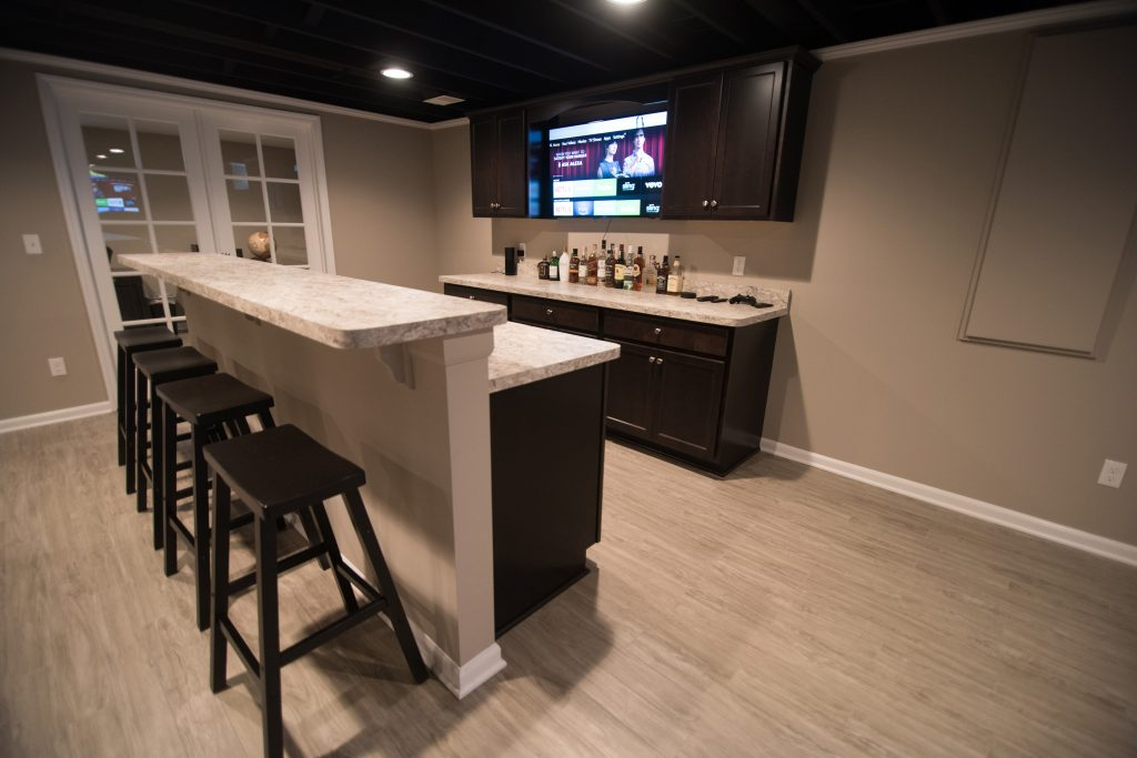 finished basement with dark cabinetry and laminate countertops