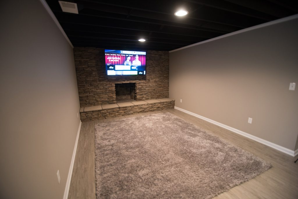 basement living room with brick fireplace and painted ceiling