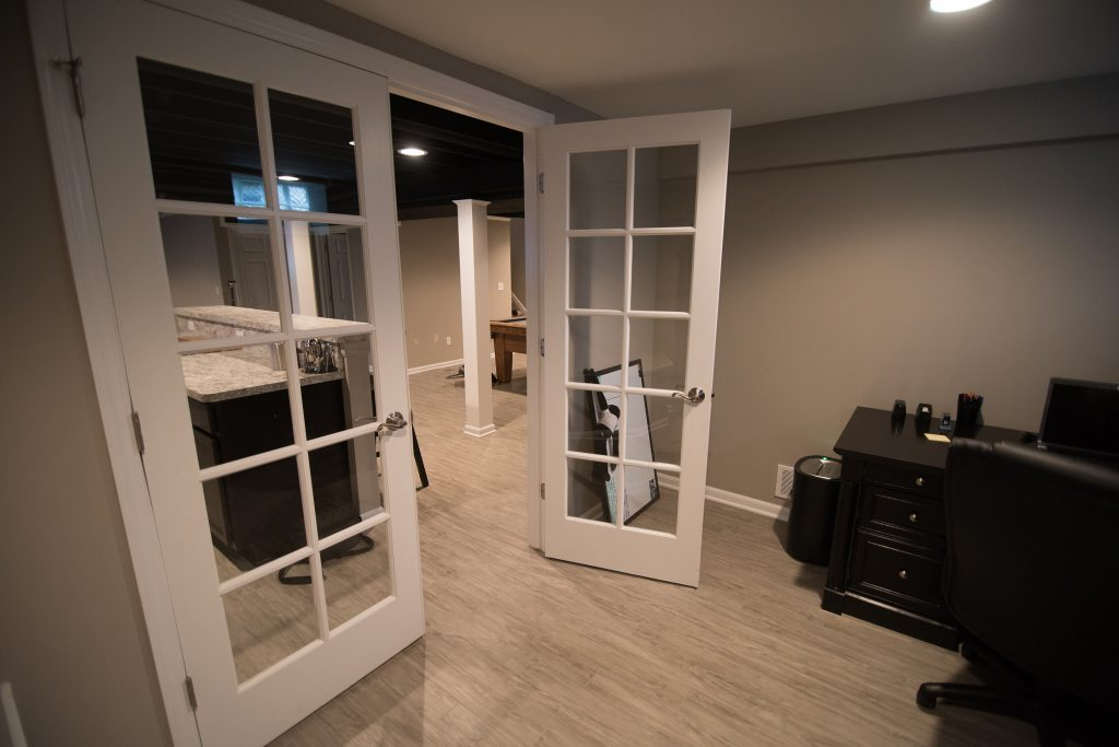 home office in basement with french doors and grey vinyl plank flooring