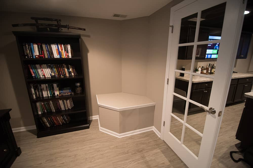 sump pump cover in basement with french doors vinyl plank flooring