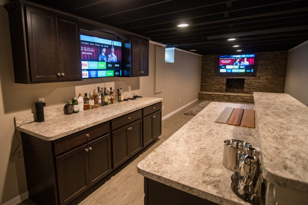 basement bar with dark cabinets and laminate countertops brick fireplace