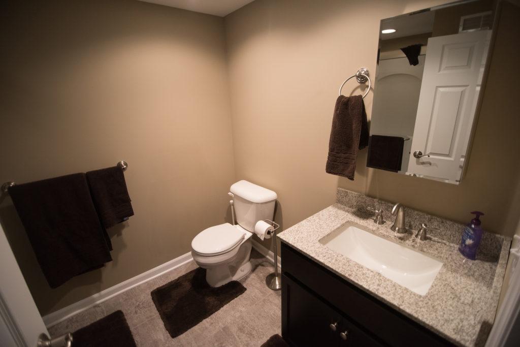 vinyl tile in basement bathroom with beige colored walls and granite countertop on vanity