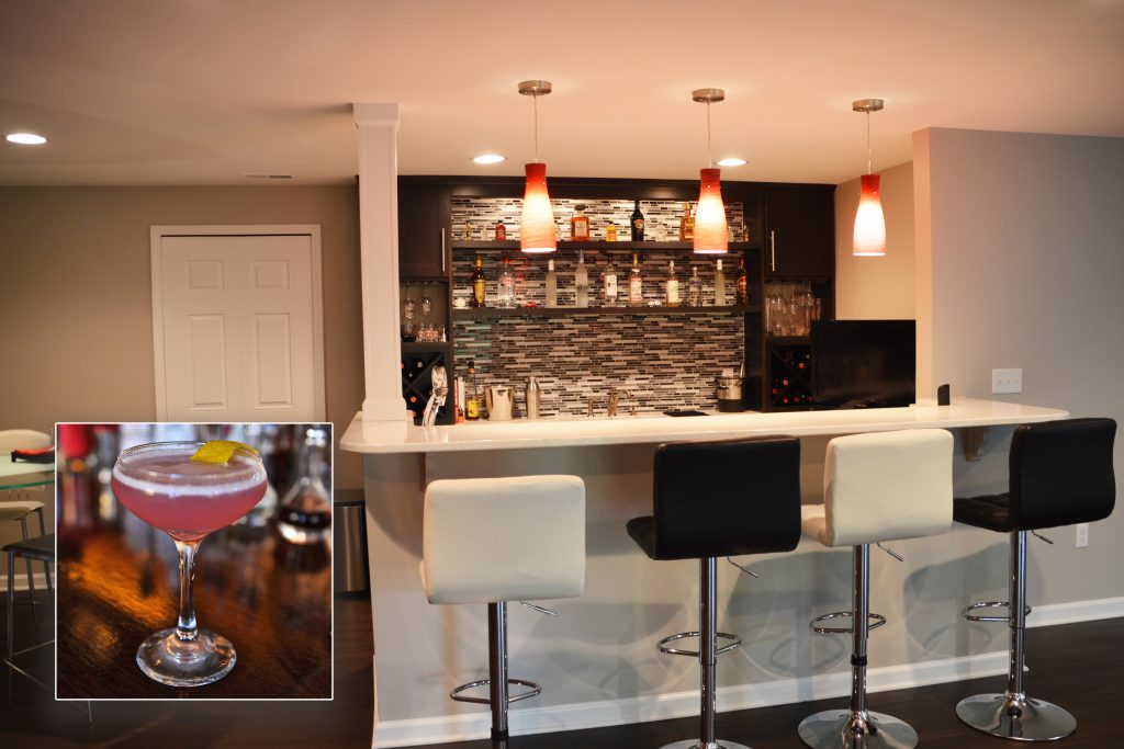 finished basement bar with dark cabinetry and pendant lights