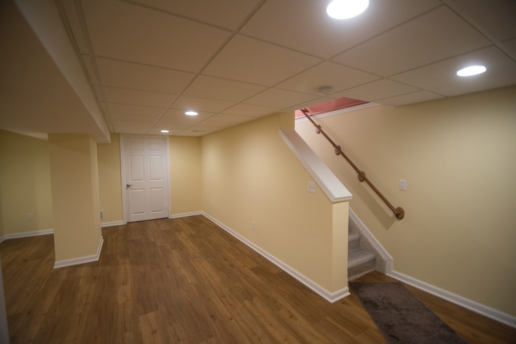 Bright yellow basement with open view staircase and vinyl plank flooring