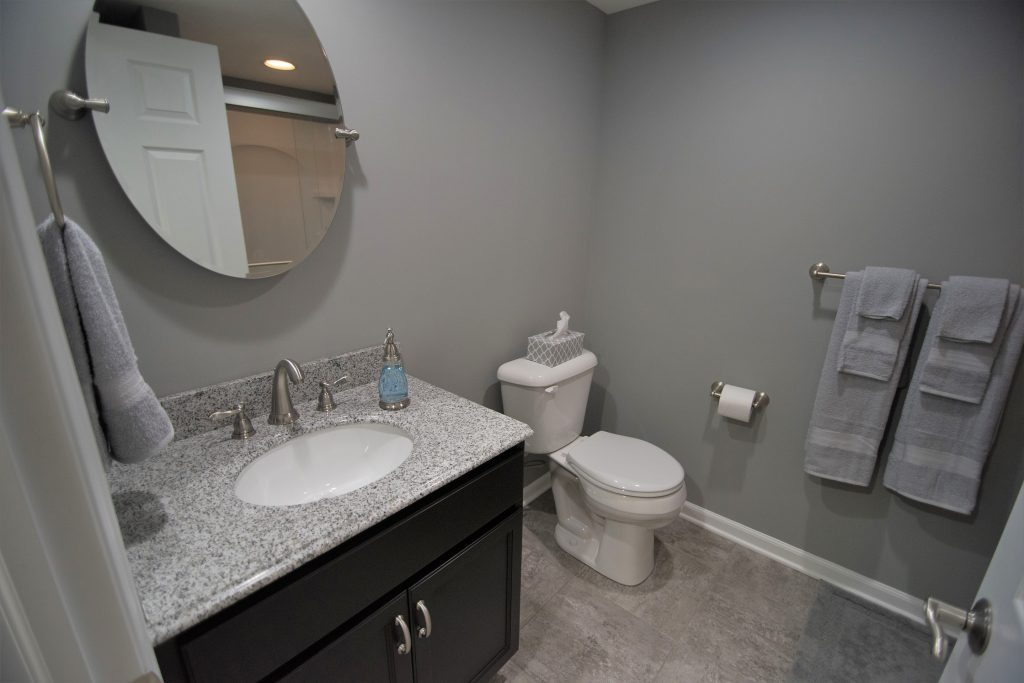 Grey remodeling bathroom with vinyl tile and granite vanity