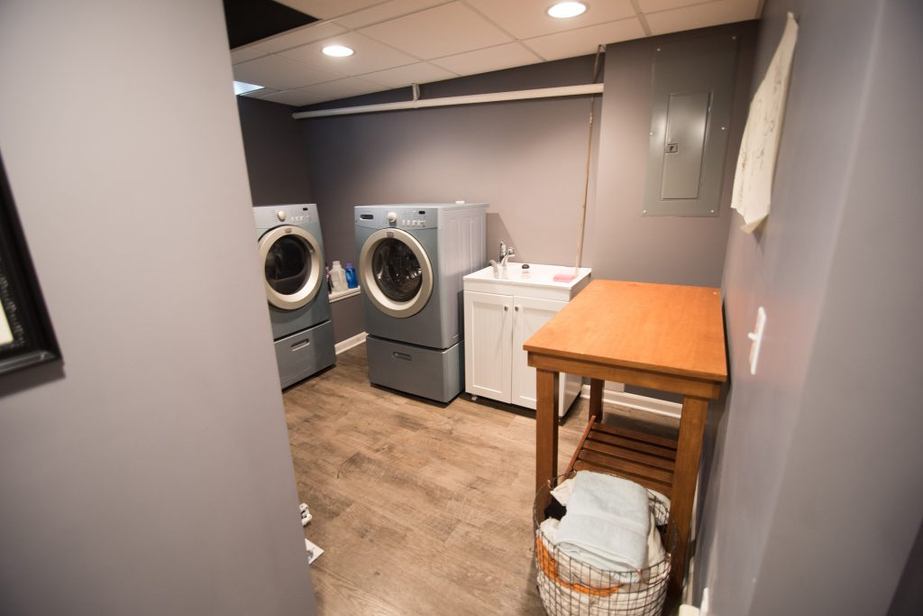 finished laundry room in basement with bright led lighting