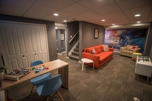 open concept finished basement designed for the kids to use with bright colors