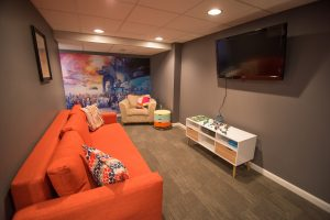 orange couch in finished basement for kids to use as playroom