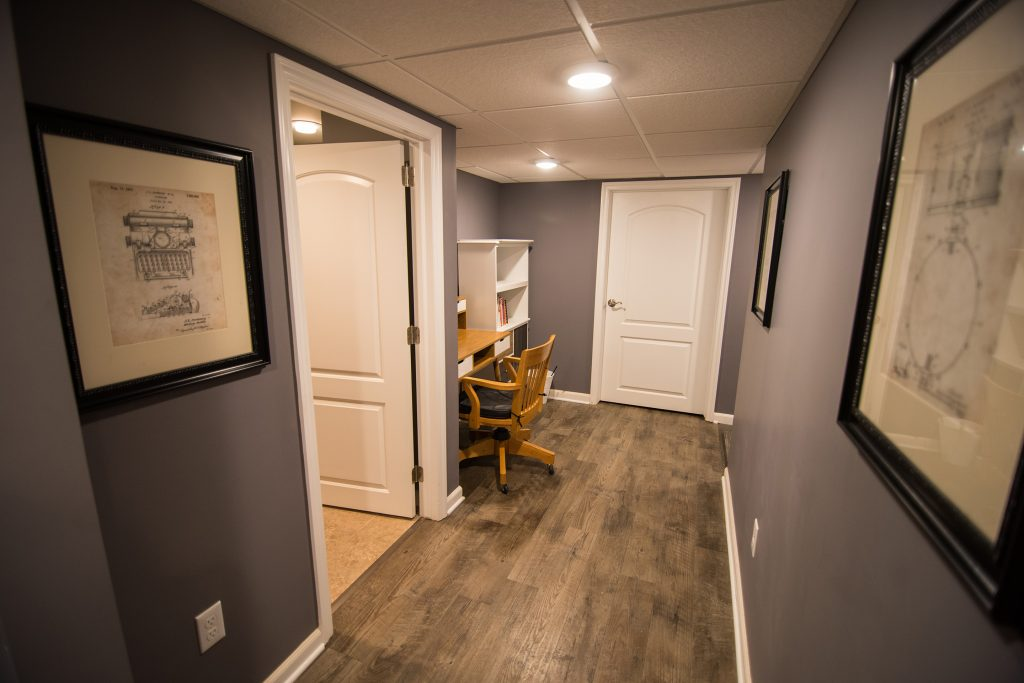 vinyl plank flooring in finished basement leading to small office