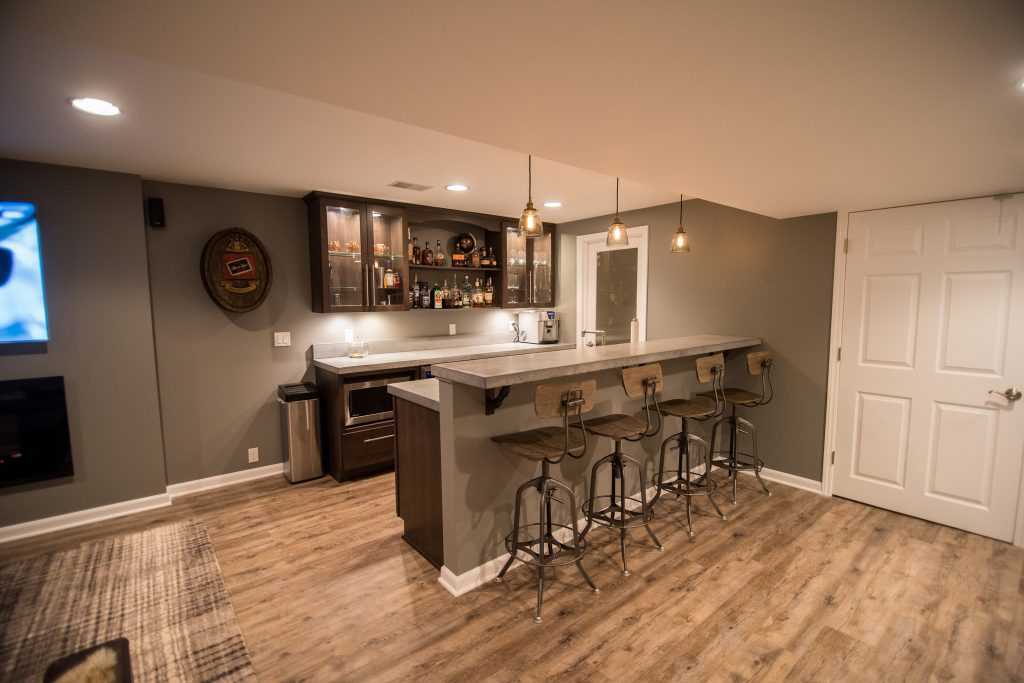 industrial rustic basement bar with concrete countertops and vinyl plank flooring