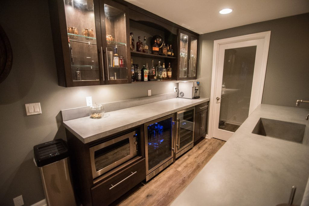 basement bar with back row of cabinets dark colored with rustic vinyl plank flooring