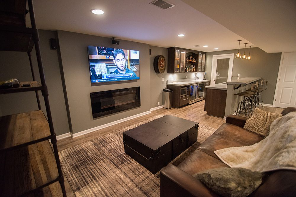 Franklin Michigan industrial finished basement design with grey walls and concrete countertops view from living room into bar