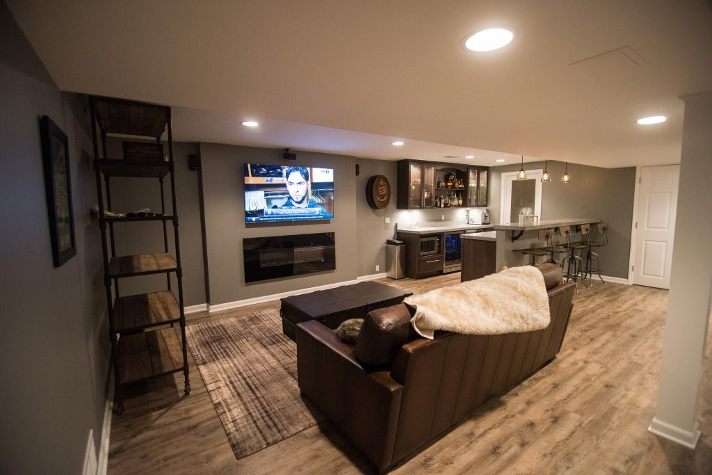 basement living room with rustic furniture and reclaimed looking vinyl plank flooring
