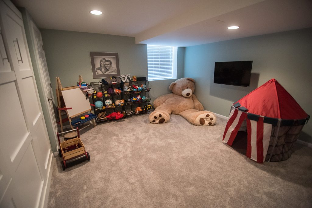 basement playroom with carpet and storage for toys