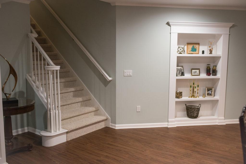 basement staircase with secret bookcase door and vinyl plank flooring